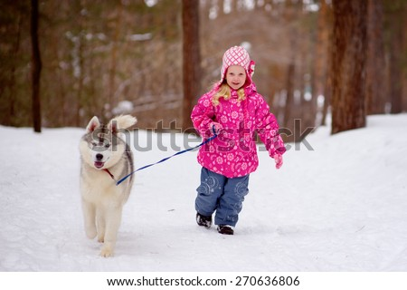 little girl running in the woods with hasky - stock photo