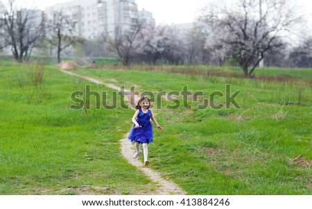 Little girl running on a rural road. - stock photo