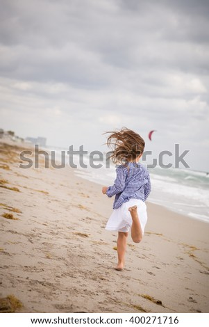 Little girl running on the ocean beach on a cloudy day. Vacation by the sea. Cute kid girl on the deserted beach. Summer, outdoors. Wind in the hair of a small girl.