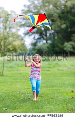 little girl running outdoor with a kite