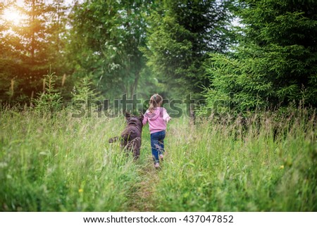 Little girl running with a dog Labrador in the woods during the summer