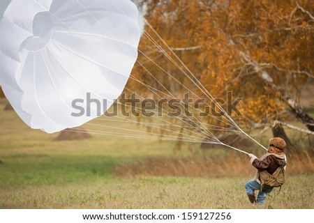 Little girl running with a parachute on the field in sunny autumn day - stock photo