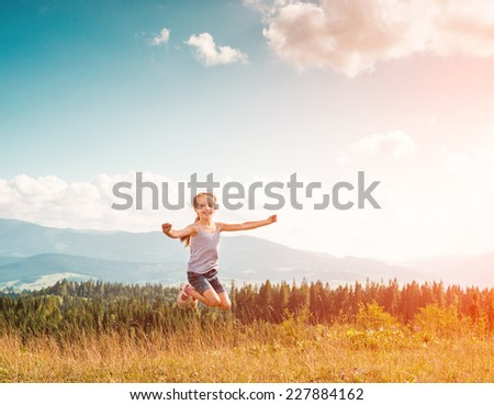 little girl runs through a beautiful meadow in the mountains. back view - stock photo