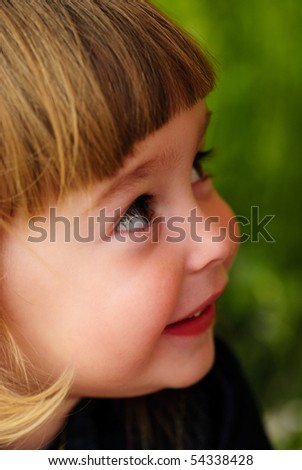 Little girl's face with hands and smile. Close up soft portrait on nature. Shalllow DOF. Focus on right eye - stock photo