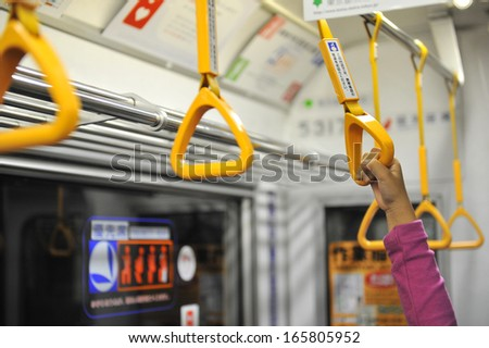 Little girl's hand holding subway strap during transportation - stock photo