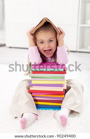 Little girl scared of school sitting with lots of books - stock photo