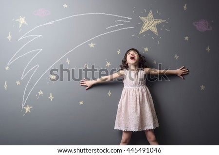 Little girl screams from pleasure to see a shooting star, the grace of the space and big planet depicted with chalk on the grey wall in studio. True emotion of happiness. - stock photo