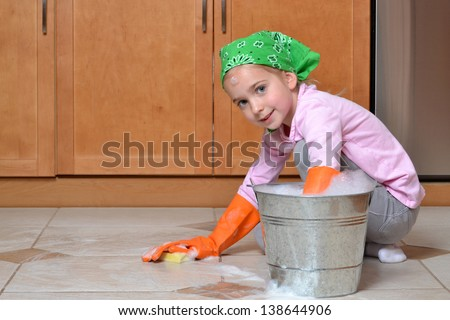 little girl scrubbing tile floor spring cleaning - stock photo