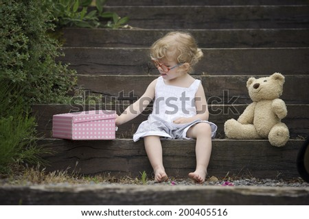 little girl seated on old wooden stairs with musical boxes - stock photo