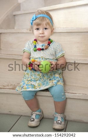 little girl seated on stairs, indoors