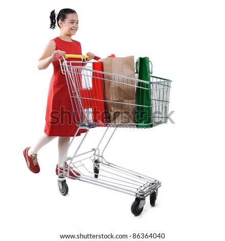 Little girl shopper in red dress with shopping cart - stock photo