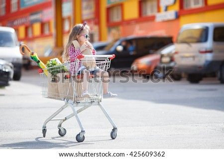 Little girl shopping with cart and bags. Child sitting in shopping cart near mall. Happy smiling child sitting in trolley cart. Sales and shopping - stock photo