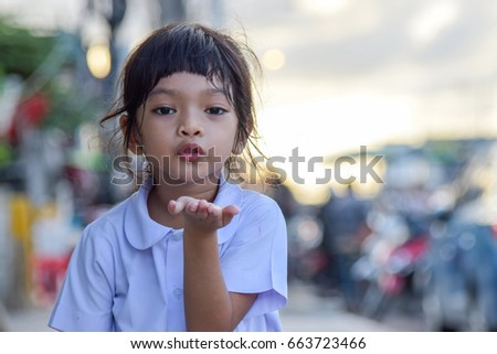 Little girl showing air kiss. looking at camera.