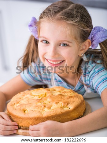 little  girl showing apple pie that she baked - stock photo