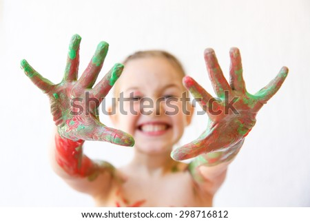 Little girl showing her hands, covered in finger paint after painting a picture and her body with it. Playfulness, creativity, permissive parenting, fun childhood concept, selective sharpness.  - stock photo