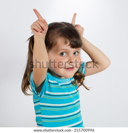 Little girl showing rabbit ears. Charming preschooler posing horns. Studio shot - stock photo