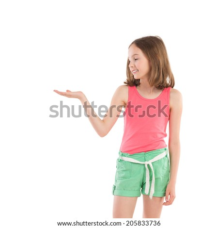 Little girl showing something on the open palm. Smiling young girl holding hand palm open and presenting product. Three quarter length studio shot isolated on white. - stock photo