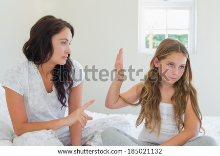 Little girl showing stop gesture to angry mother while sitting in bed at home - stock photo