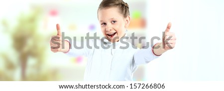 Little girl showing the thumbs up isolated on background - stock photo