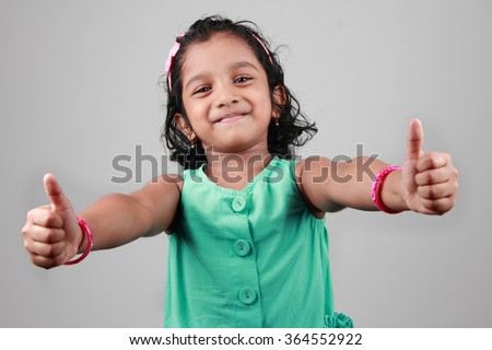Little girl shows thumbs up symbol - stock photo