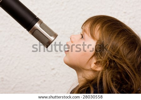 Little girl singing a song in a microphone - stock photo
