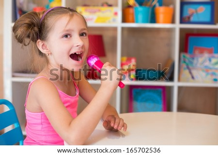 Little girl singing into a toy microphone sitting at a table in the game room
