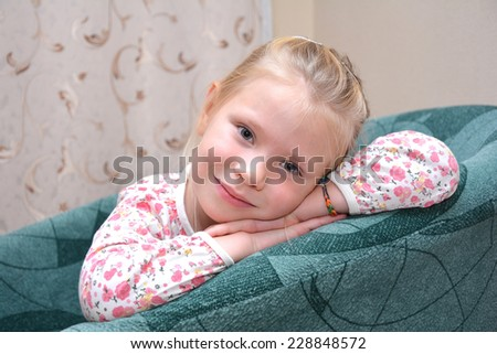 little girl siting on a chair