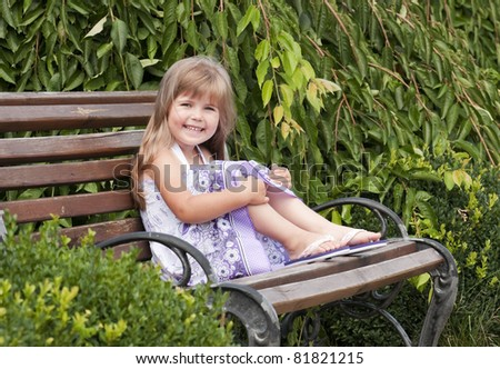Little girl siting on the bench in the park