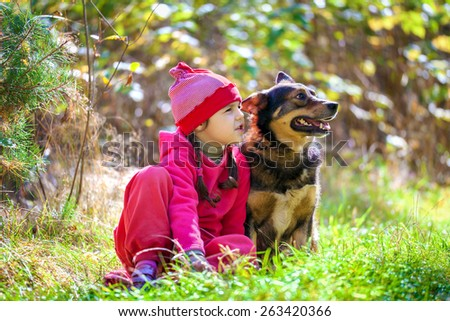 Little girl siting with dog on the lawn in the forest - stock photo