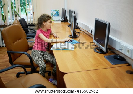 Little girl sits alone at table with computer monitor at computer room. - stock photo