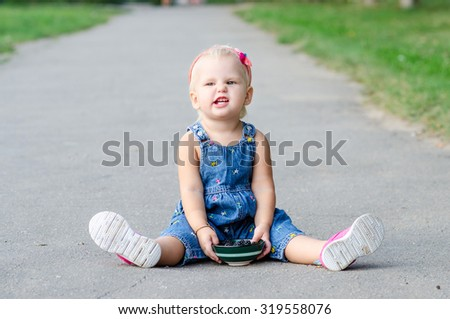 Little girl sits and eats on the road - stock photo