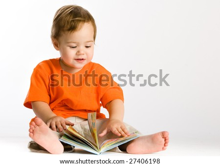 Little girl sits and reading book - stock photo