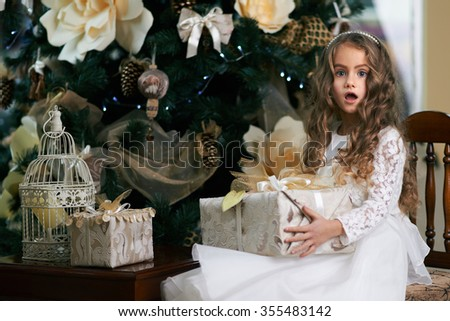 Little girl sits near Christmas tree with a gift and scared. - stock photo