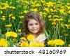 Little girl sits on a glade with dandelions - stock photo