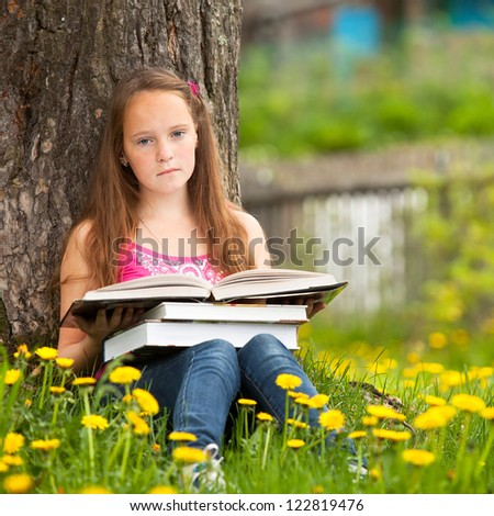 Little girl sits on a grass and dreams while reading a book - stock photo
