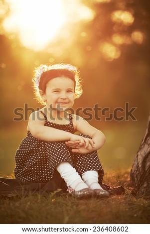 little girl sits on sunset - stock photo