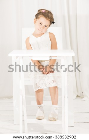 Little girl sitting alone at white table cafe in white room. Girl in a white dress was left alone. Girl waiting for mum and dad sitting on white chair at white table - stock photo