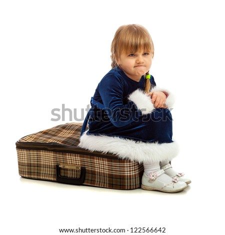 Little girl sitting angry on big travel suitcase isolated on white - stock photo