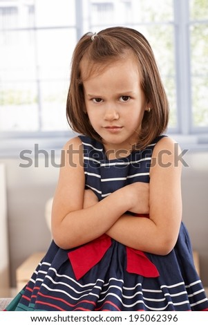 Little girl sitting arms crossed, sulking - stock photo