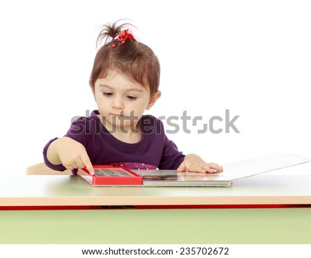 Little girl sitting at a table and read e-books. Montessori Wednesday.White background, isolated photo. - stock photo