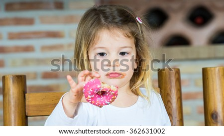 Little girl sitting at a table eating breakfast pastries and chocolate and playing