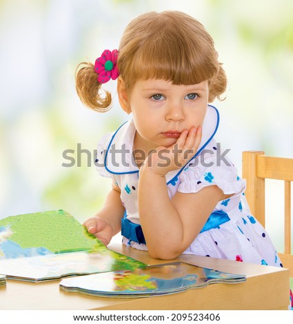Little girl sitting at a table leaning on his hand .The concept of childhood and child development - stock photo
