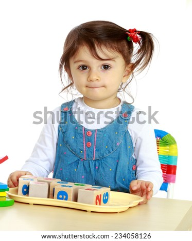 Little girl sitting at a table playing cubes on which numbers are written. Isolated on white background. - stock photo