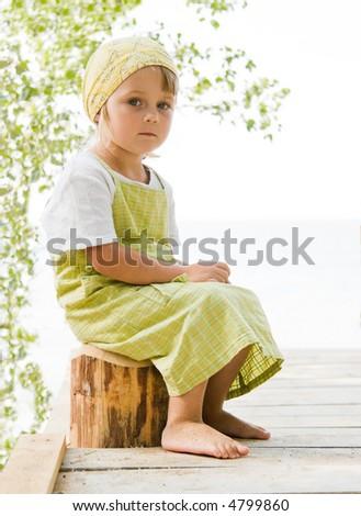 little girl sitting at beam - stock photo