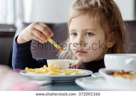 little girl sitting at table and eating French fries from your plate. - stock photo
