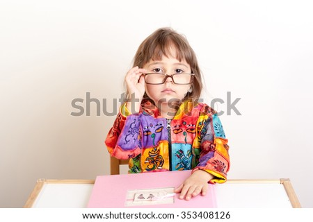 little girl sitting at the desk and looking over her glasses - stock photo