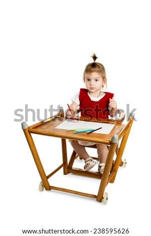 Little girl sitting at the table and draws a pencil and looking at the camera isolated on a white background - stock photo