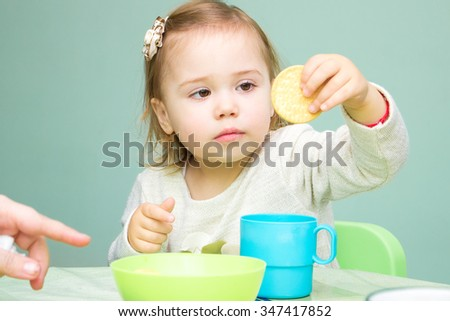 Little girl sitting at the table drinking tea and eating cookies - stock photo