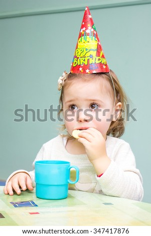 Little girl sitting at the table in her birthday drinking tea and eating cookies - stock photo