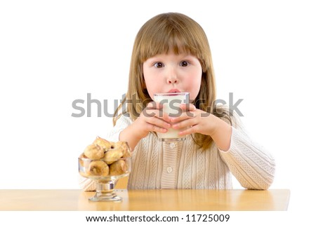 Little girl sitting at the wooden table having Breakfast isolated on white - stock photo
